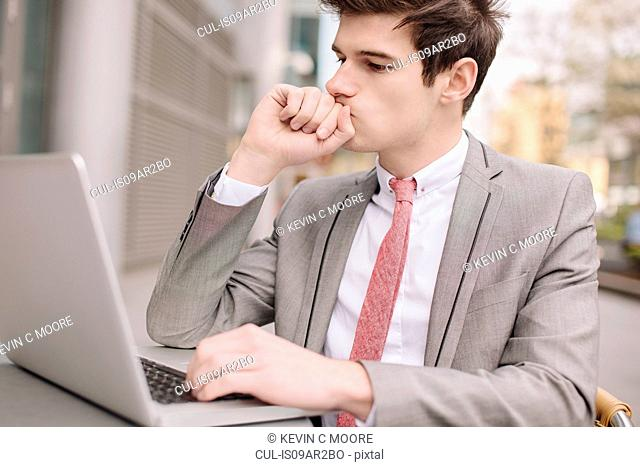 Worried young city businessman using laptop at sidewalk cafe