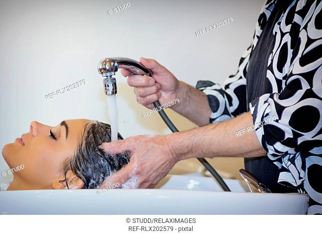 Hairdresser washing shower head hair customer sink