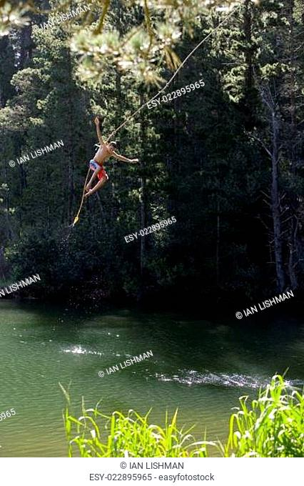 Boy (9-11), in swimming shorts, letting go of rope swing above lake