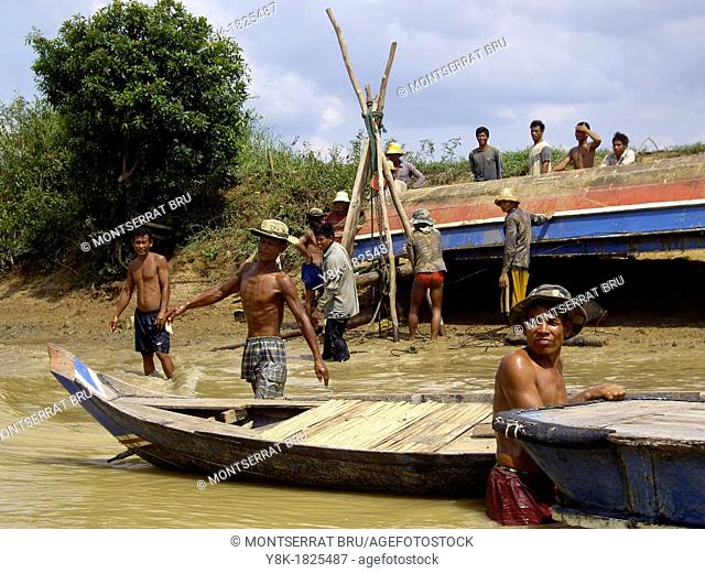 Fishermen fixing a boat at Tonle Sap Lake in Cambodia