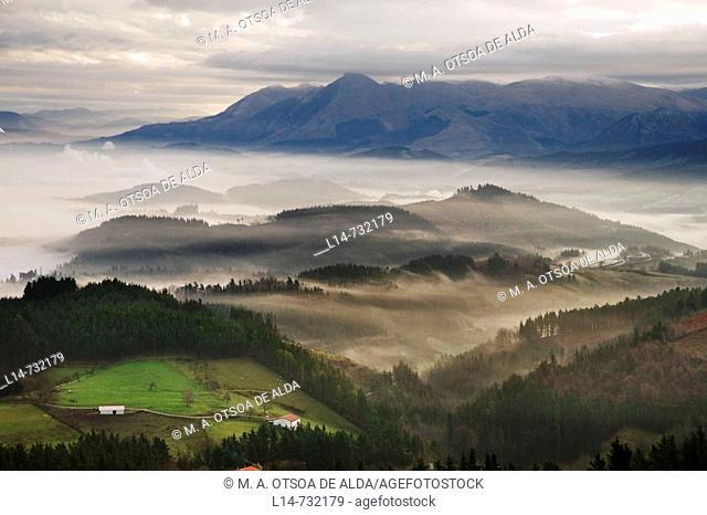 Fog over Goierri valley with Txindoki mountain of the Aralar mountain range in background. Guipuzcoa, Basque Country, Spain
