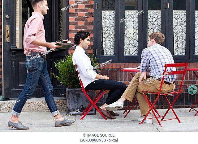 Waiter bringing coffee to men outside cafe