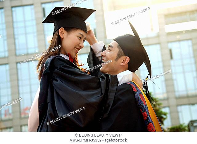 Two university students in graduation gown embracing