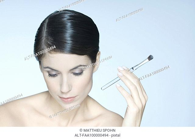 Woman holding eye shadow brush, looking down