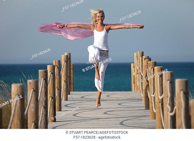 Healthy young woman skipping down a boardwalk
