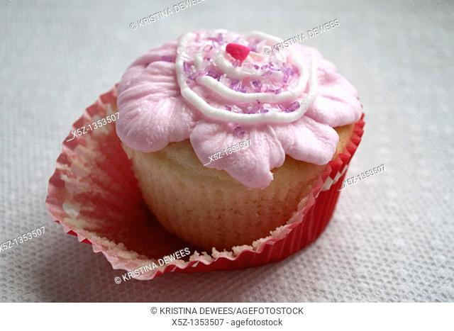 A fancy frosted cupcake half unwrapped