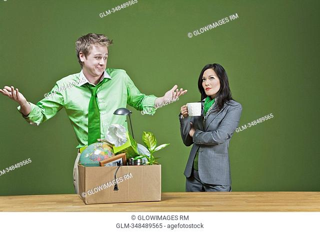 Businessman with his belongings and a businesswoman holding a cup of coffee