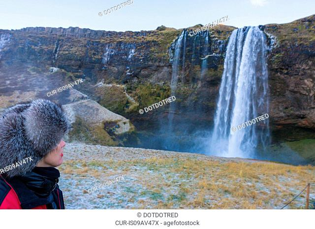 Woman watching Seljalandsfoss waterfall, South West Iceland