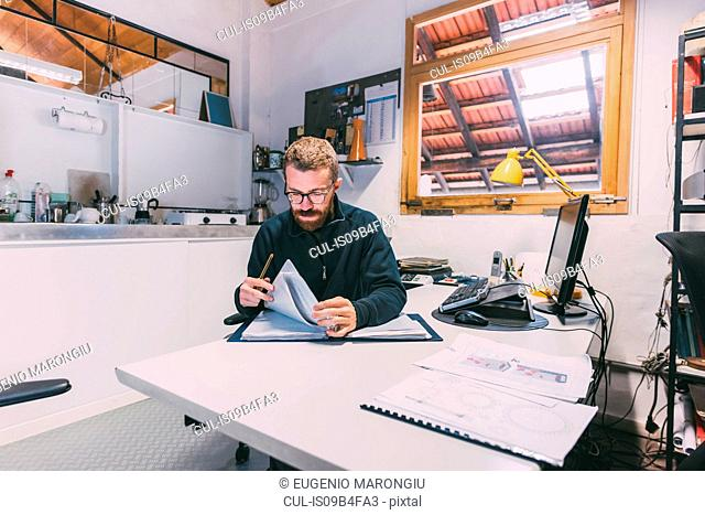 Male metalworker reviewing designs in forge office