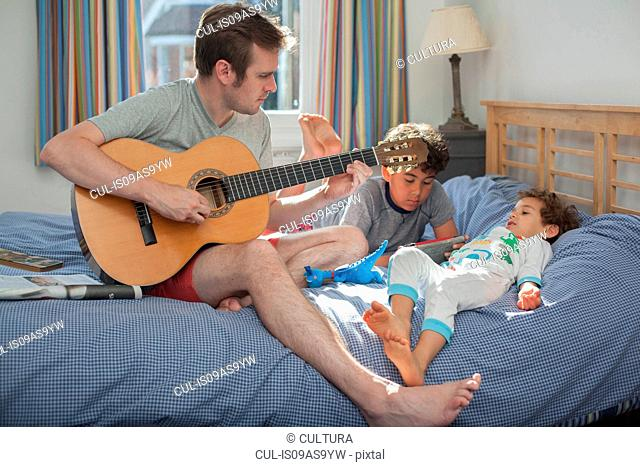 Father playing guitar while two sons relax on bed