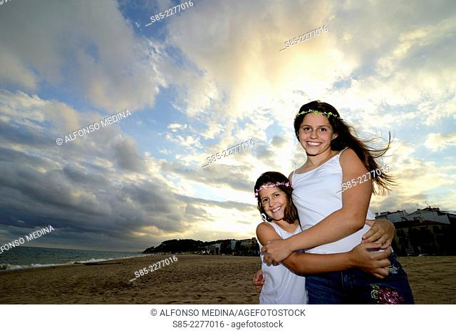 girls on the beach hugging and playing