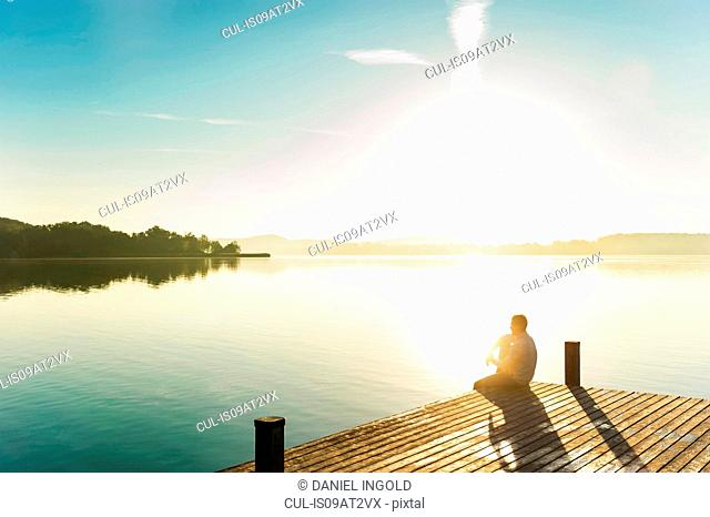 Young man sitting on corner of pier of sunlit lake, Woerthsee, Bavaria, Germany