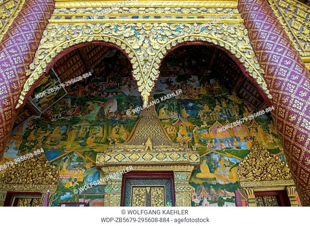 Detail with frescoes and door of Wat Xieng Muan (Xieng Muan Vajiramangalaram) a Buddhist temple in the UNESCO world heritage town of Luang Prabang in Central...