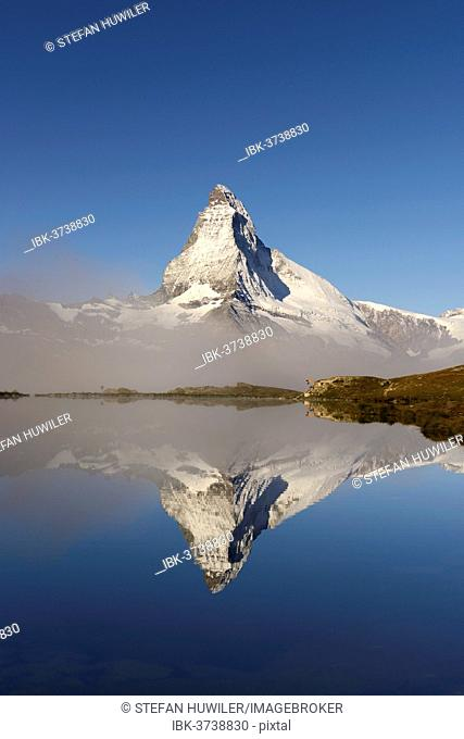 Matterhorn reflected in Lake Stellisee, with fog, Valais Alps, Canton of Valais, Switzerland