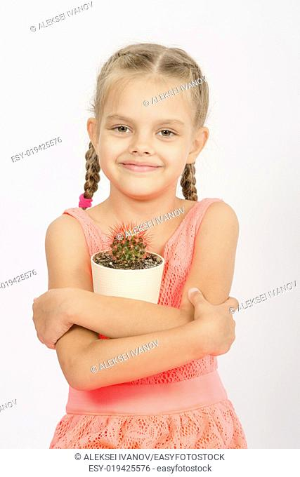 Six year old girl standing with a cactus in a pot, isolated on a light background