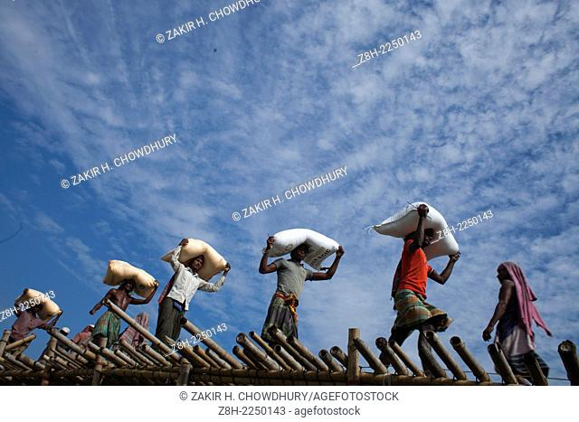 worker carrying paddy on their head