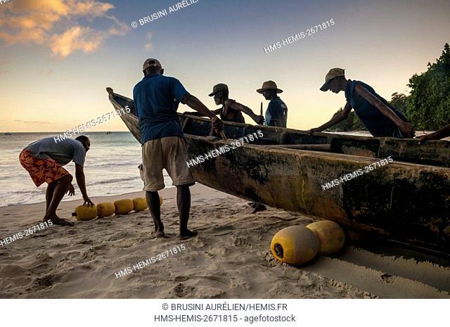 Seychelles, Mahe Island, Beau Vallon, group of fishermen taking sea in their Katiolo (traditional fishing pirogue)
