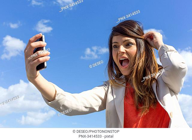 Pretty brunette woman doing a selfie with smartphone