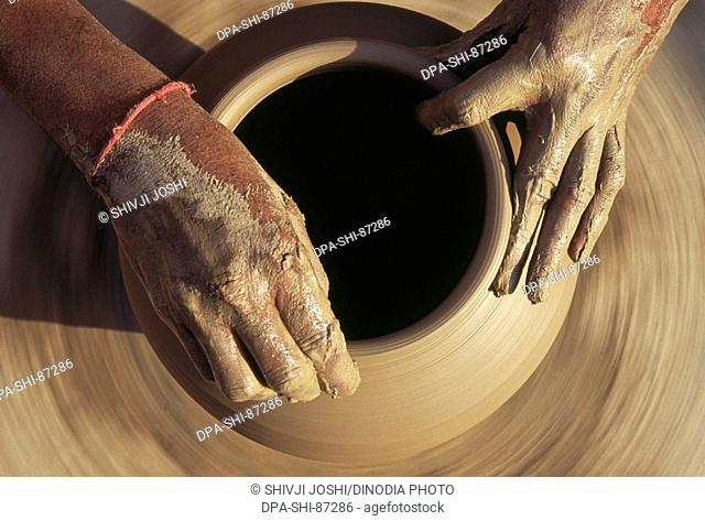 Pottery , potter giving shape to clay pot on wheel , Bikaner , Rajasthan , India