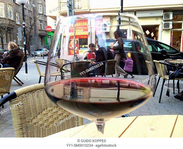 Sun and Moon Restaurant, Sofia, Bulgaria. Glass of red wine, with people sitting behind it