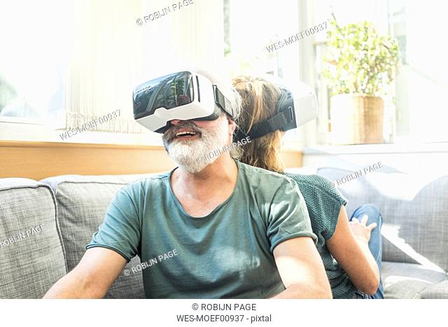 Happy mature couple sitting on couch at home wearing VR glasses
