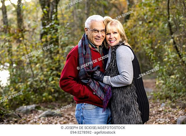 A happy 65 year old man and a 59 year old blond woman hugging in a forest setting, smiling at the camera
