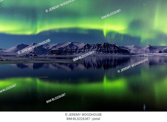 Aurora Borealis in night sky over landscape