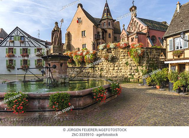 picturesque place in the old village Eguisheim, Alsace, France, scenic square with castle Château de Saint-Léon-Pfalz and well