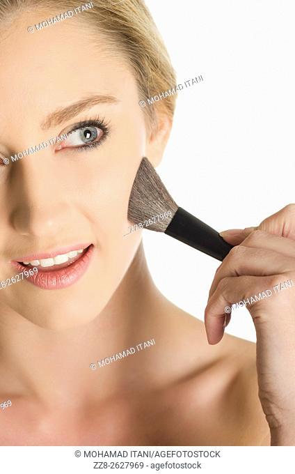 Beautiful young woman applying blusher to her face