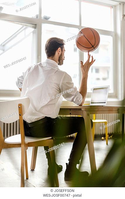 Back view of young man sitting at desk looking at laptop while balancing a basketball on his finger