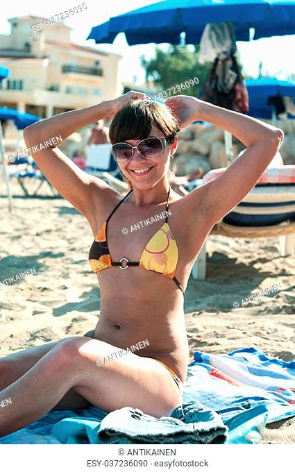 Joyful brunette woman in sunglasses sitting on sandy beach with hands up