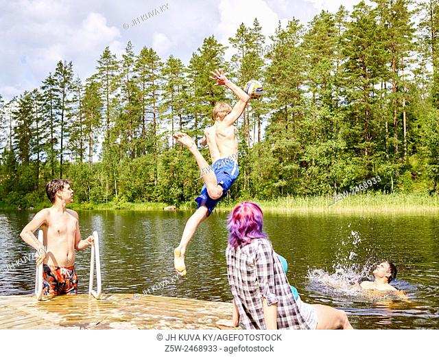 The group of the friends chilling out on the beach, summer day. Shot in southern Finland