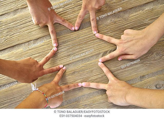 Star shape with six hand fingers on a beach wood