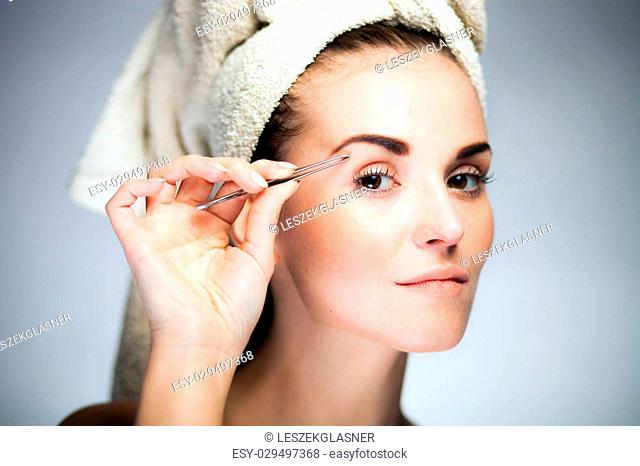 Beauty fresh model girl shaping eyebrows with tweezer