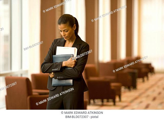African businesswoman holding paperwork in hotel lobby