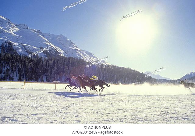 Jockeys races their horses across ice course in winter in mountain setting