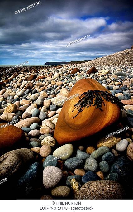 England, Cumbria, Seascale, A close up of red rocks on the pebble beach at Seascale