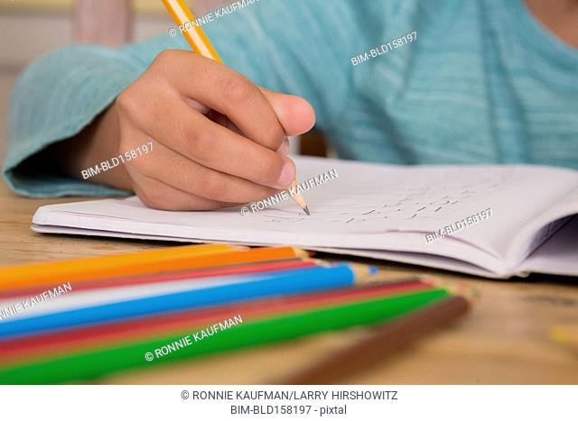 Close up of boy writing in notebook