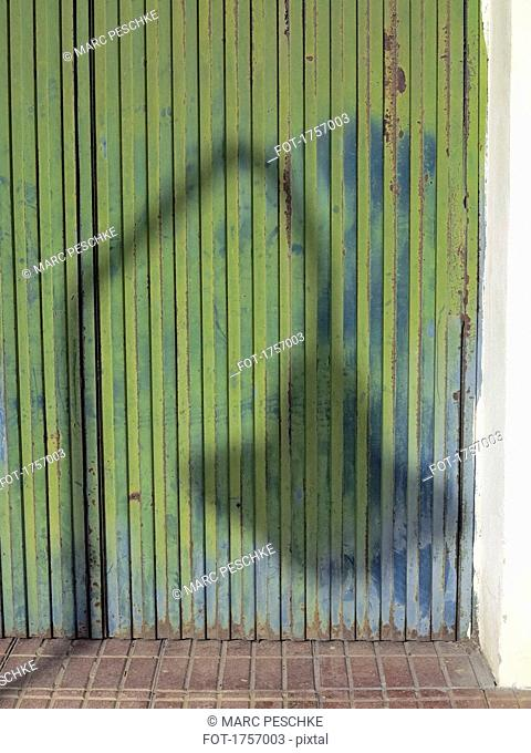 Shadow of street light on rusty corrugated green iron