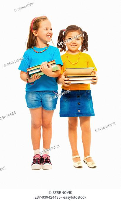 Two happy little girls Asian and Caucasian black and light haired with stack books standing isolated on white, full height portrait
