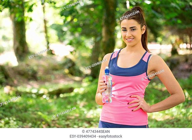 Fit cute woman wearing sportswear holding bottle posing in a forest