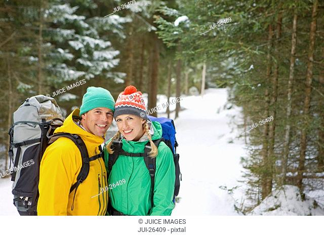 Portrait of happy couple with backpacks in snowy woods