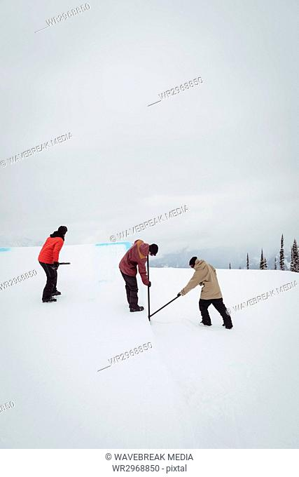 Group of man cleaning snow in ski resort