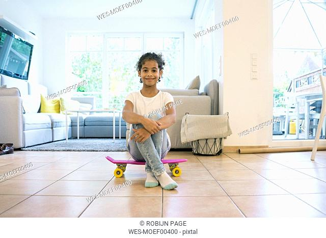 Little girl sitting on skateboard, looking proud