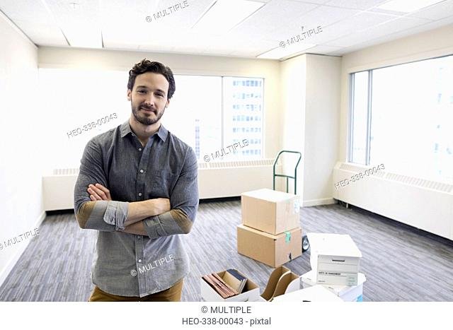 Portrait confident businessman with cardboard boxes in new office