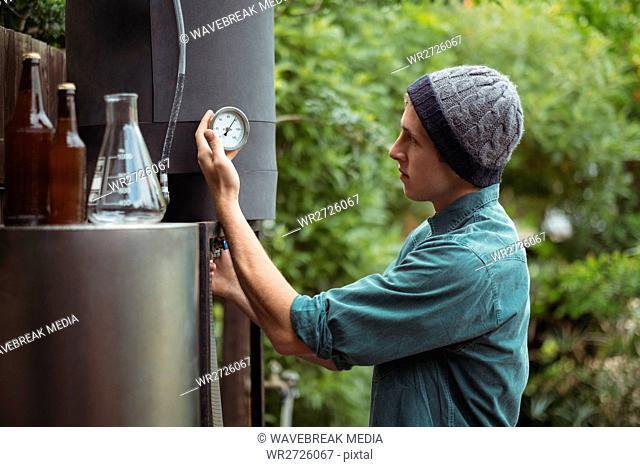 Man checking gauge while making beer