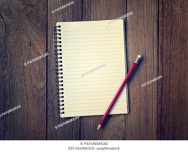 top view image of blank notebook on wooden, vintage filtered and toned