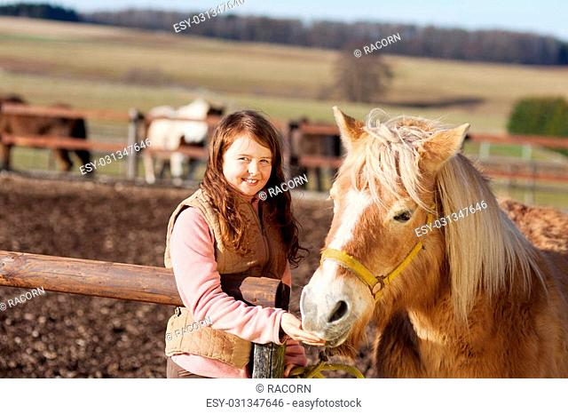 Portrait of a happy smiling girl feeding her horse treats