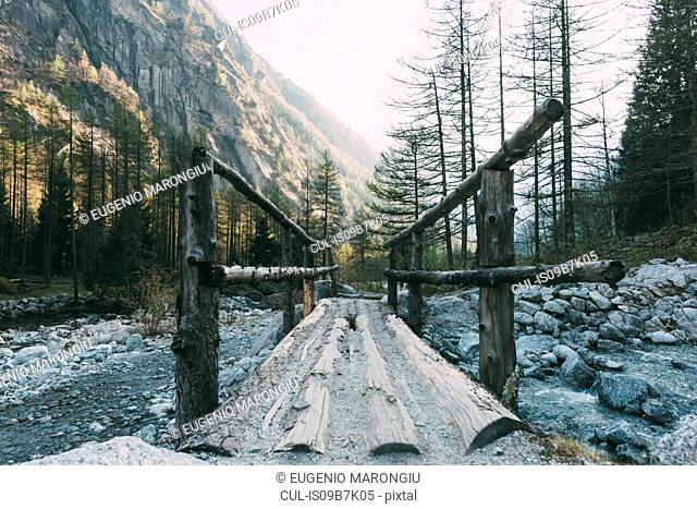 Wooden footbridge crossing mountain river, Mello, Lombardy, Italy