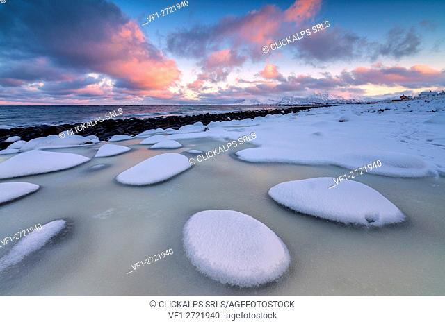 Dawn on the cold sea surrounded by snowy rocks shaped by wind and ice at Eggum Vestvagøy Island Lofoten Islands Norway Europe